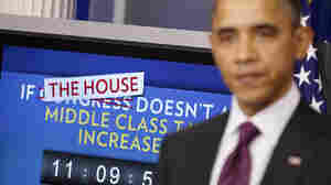 President Obama speaks in the White House's Brady Briefing Room on Tuesday. Behind the president, a ticking clock counts down the time until taxes will go up if Congress can't reach an extension deal on payroll tax cuts.