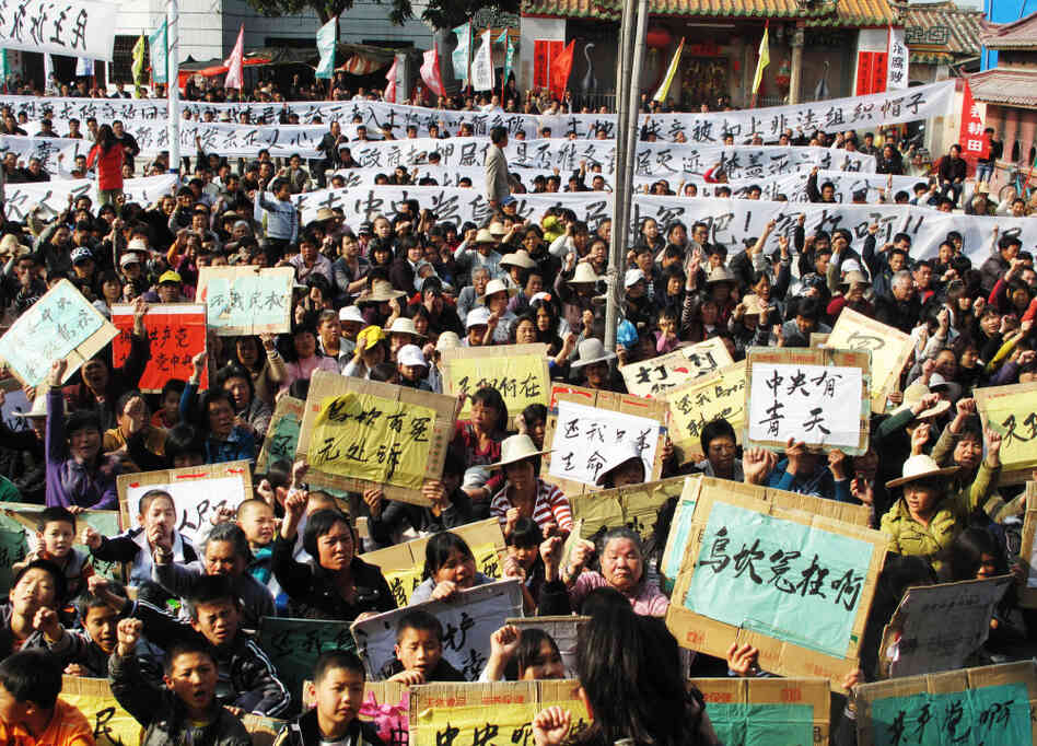 In a rare mass protest, thousands of people from the besieged village of Wukan, China, gather to demonstrate against what they say are illegal land seizures by the government. The village