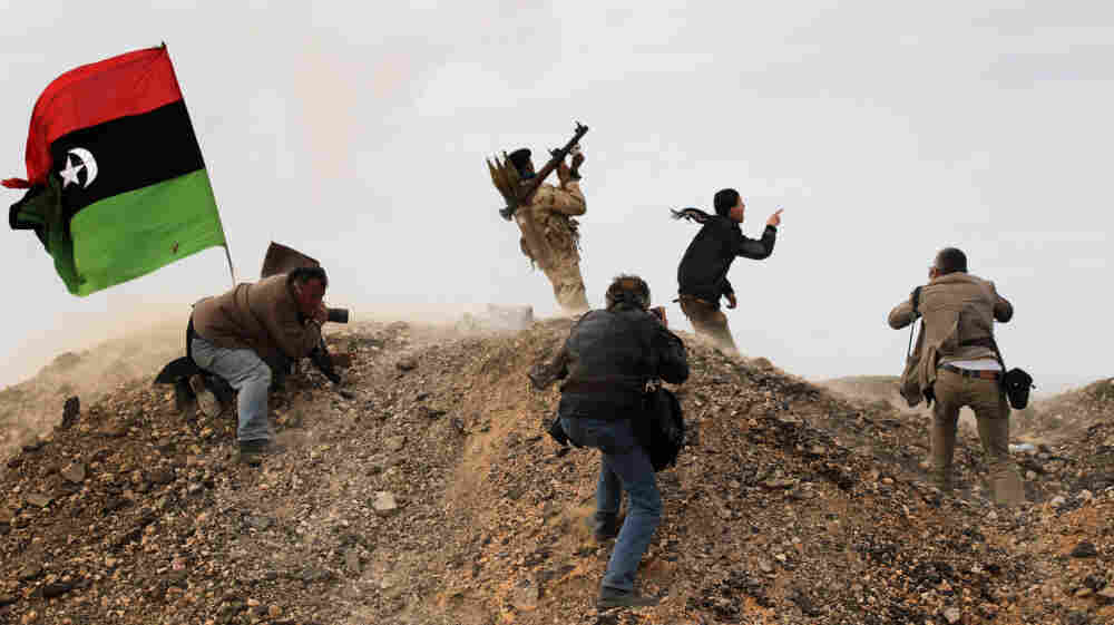 Photojournalists, including New York Times staff photographer Tyler Hicks, photograph Libyan rebels on March 10 in Ras Lanuf, Libya. Hicks and three other Times journalists — Stephen Farrell, Lynsey Addario and Anthony Shadid — were released March 21 after being held captive by Libyan forces.