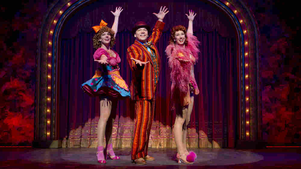 """Danny Burstein, as Buddy Plummer, performs """"Buddy's Blues,"""" the high-energy song-and-dance number at the end of Follies, with Jenifer Foote (left) and Kiira Schmidt."""