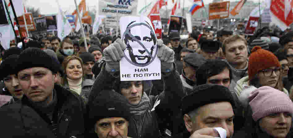"A protester holds a portrait of Putin with the words read as "" we are going different ways"" during a mass rally to protest against alleged vote rigging in Russia's parliamentary elections in Moscow, Russia, Saturday, Dec. 10, 2011."