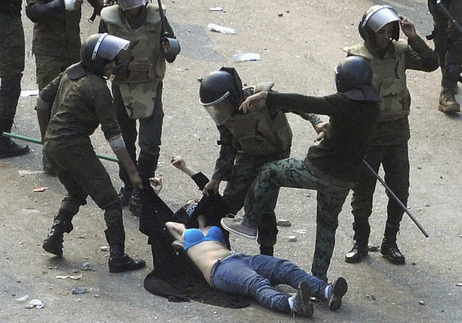 Egyptian army soldiers arrest a female protester during clashes at Tahrir Square in Cairo on Dec. 17.