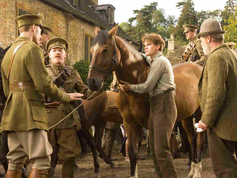 Capt. Nicholls (Tom Hiddleston, left) and Sgt. Perkins (Geoff Bell) prepare to take Joey away to the battlefield.