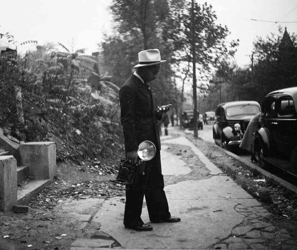 "Charles ""Teenie"" Harris, holding camera and standing on sidewalk, circa 1938."