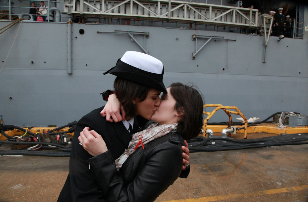 Petty Officer 2nd Class Marissa Gaeta, left, kisses her girlfriend of two years, Petty Officer 3rd Class Citlalic Snell at Joint Expeditionary Base Little Creek in Virginia Beach, Va. Gaeta's ship returned from 80 days at sea on Wednesday.