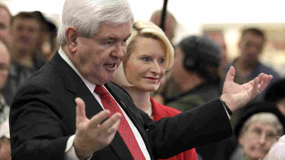 Republican presidential candidate Newt Gingrich, accompanied by his wife, Callista, speaks at a Hy-Vee store in Mount Pleasant, Iowa, on Tuesday.