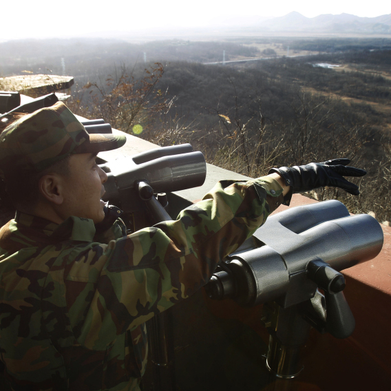 A South Korean soldier points to North Korea from a lookout post in the border village of Panmunjom in the demilitarized zone (DMZ) on Thursday.