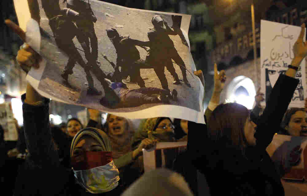 Angered by recent violence against them in clashes between army soldiers and protesters, Egyptian women — one carrying a poster with a picture of a woman who was assaulted by soldiers — chant anti-military slogans during a rally that ended in Cairo's Tahrir Square on Tuesday.