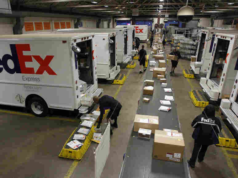 Couriers load packages onto vehicles as other packages move down the belt at the FedEx station in Marina del Rey, Calif. Online shopping made a big mark on FedEx's business this year, as more retailers are offering later-guaranteed arrivals than ever.