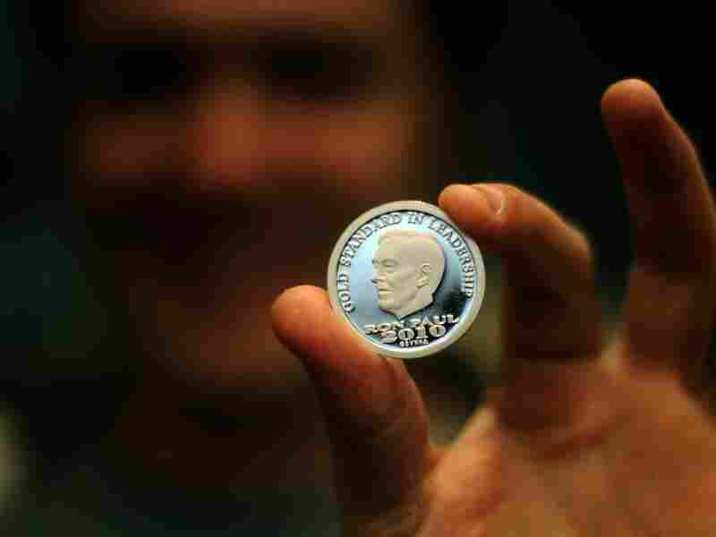 In Paul We Trust? A supporter shows a coin with Republican presidential hopeful Ron Paul's face on it during a town hall meeting in Mt. Pleasant, Iowa, on Dec. 21, 2011.