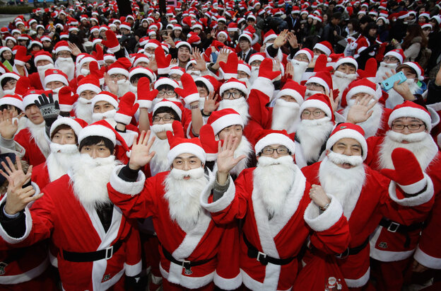 South Koreans wear Santa Claus outfits and hold gifts to promote Christmas at a charity event in Seoul on Friday.
