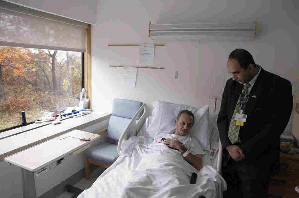 Ramadon Aliah, a 37-year-old Libyan freedom fighter wounded in Misrata, Libya lies in his bed talking with a translator at the Spaulding Rehabilitation Hospital in Salem, Mass., in November. Of the 22 Libyans who came to Spaulding in late October, 16 are still there and the rest are expected to be discharged by February.