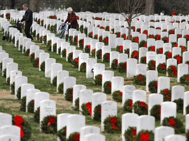 Visitors walk among gravestones adorned with seasonal Christmas wreaths at Arlington National Cemetery.