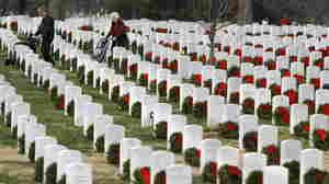 Visitors walk among gravestones adorned with seasonal Christmas wreaths at Arlington National Cemetery.