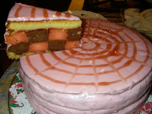 A punch torte: pink-glazed sponge cake with layers soaked in rum and citrus syrup.