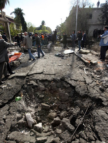 A crater left by an explosion at the site of a suicide attack today in Damascus.