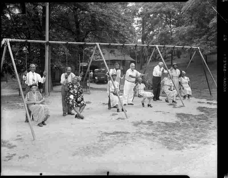 Men, including T. Hamilton, Len Holland, James Hughes and Thomas Williams, stand behind women seated on swings at Highland Park picnic, August 1952.