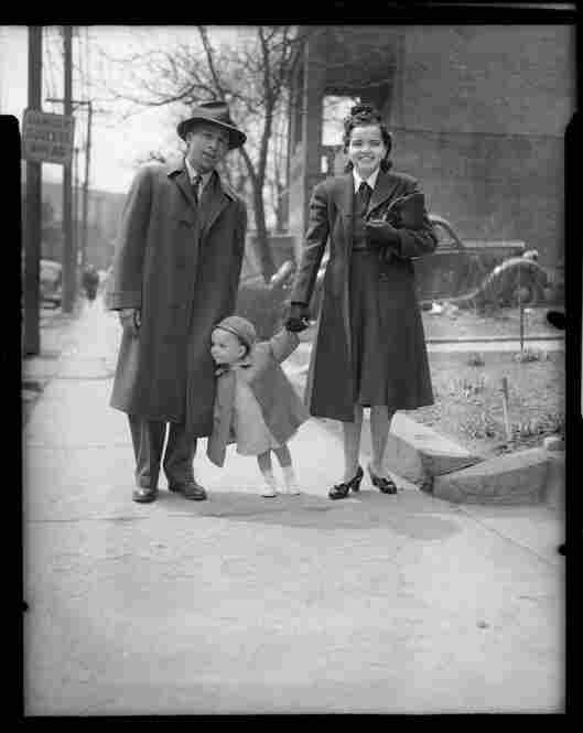 A man and woman hold hands with small child on the sidewalk, circa 1940-1946.