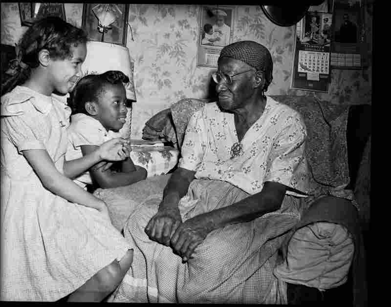 "Two girls with former slave Sabre ""Mother"" Washington, circa 1950-1955."