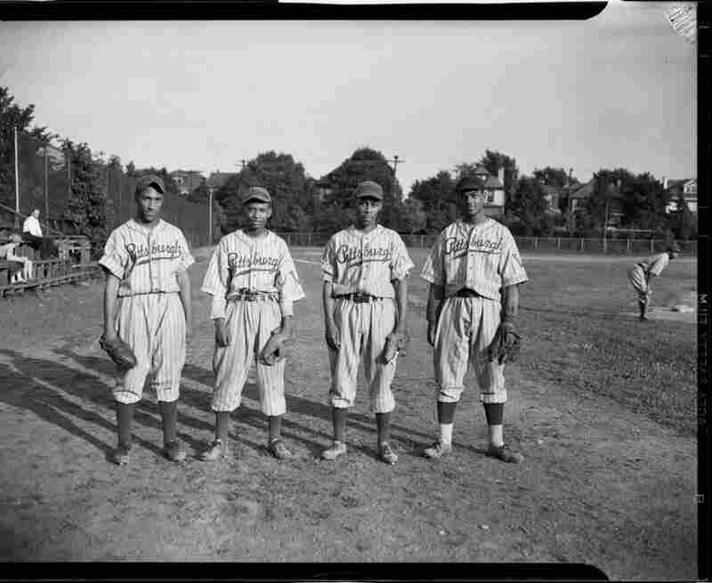 Four Pittsburgh Crawfords baseball players, Peatross, Johnson, Daniels, and Atkins, stand on field, May 1945.