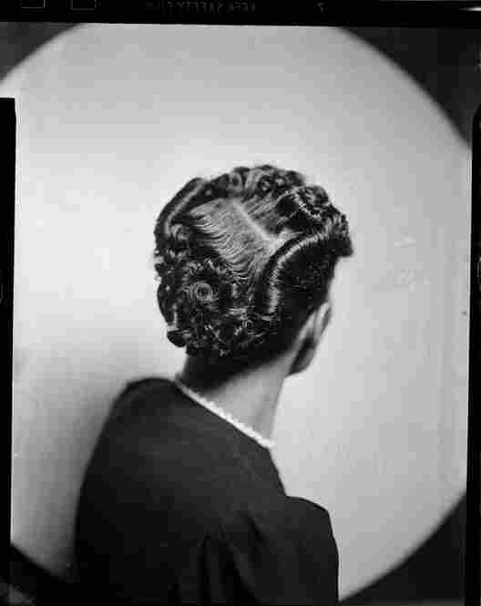 A woman models a hairstyle in Harris Studio, circa 1938-1945.