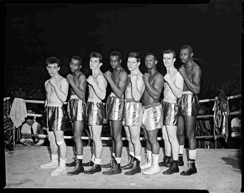 Boxers, possibly Golden Gloves contenders, line up in a boxing ring, circa 1955.