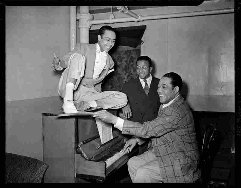 Duke Ellington at piano, with dancer Honey Coles and Billy Strayhorn looking on, in the Stanley Theatre, circa 1942-1943.