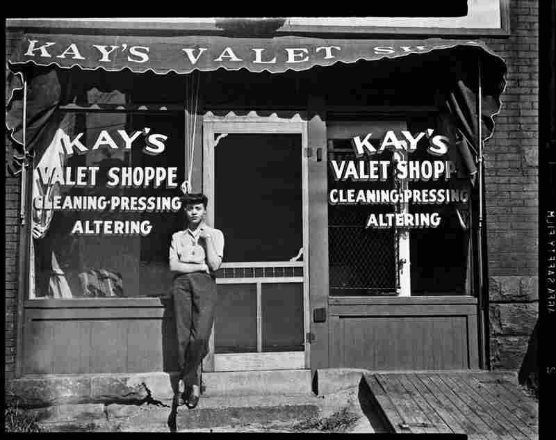 A woman stands outside Kay's Valet Shoppe, circa 1938-1945.