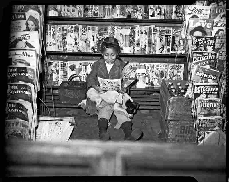 A little girl reads a comic book at a newsstand, circa 1940-1945.