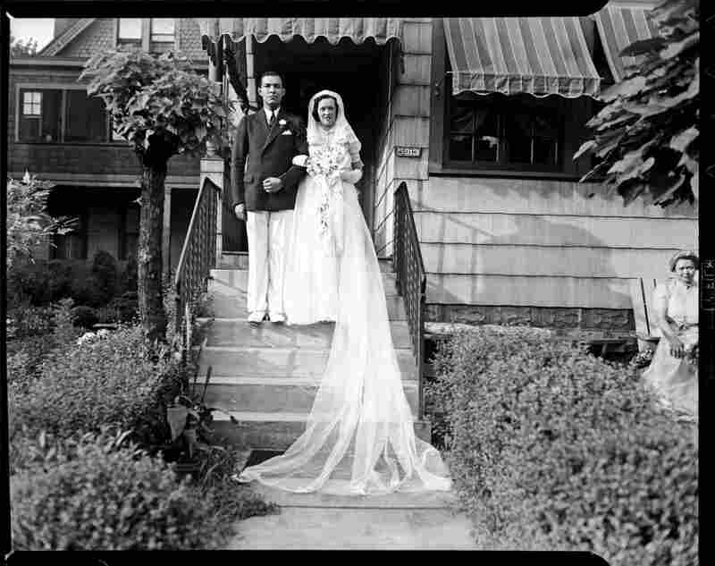 Roland M. Sawyer and Aileen Eckstein Sawyer pose on their wedding day on steps of The Thimble Shop in Highland Park, August 1938.