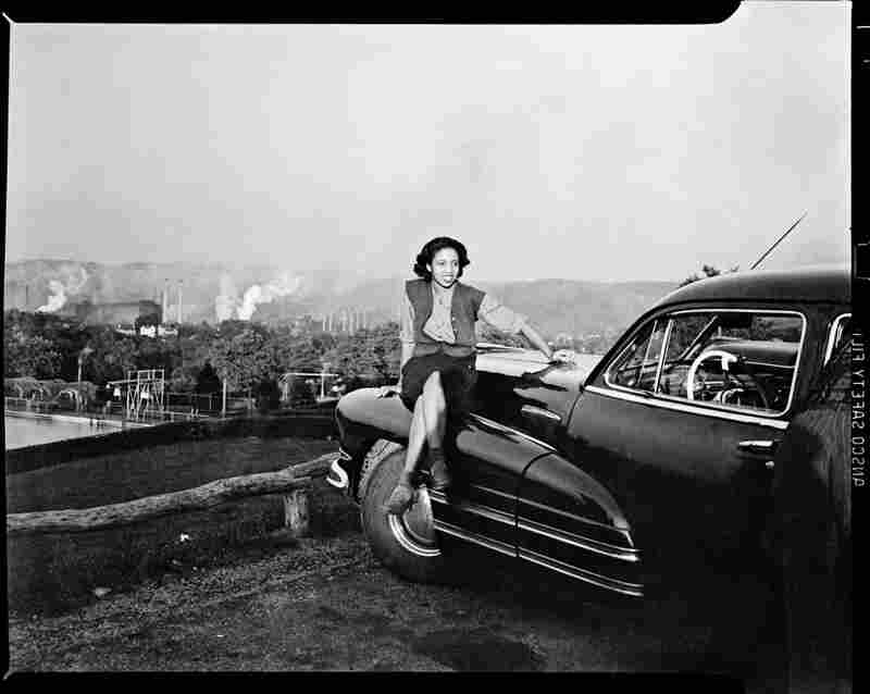 A woman sits on a car, with a steel mill in the background, circa 1940-1946.
