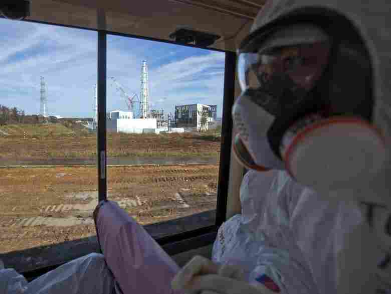 An official from the Tokyo Electric Power Co. (right), wearing a protective suit and mask, rides on a bus taking journalists by the crippled Fukushima nuclear power station in northeast Japan in November. Japanese officials say the plant is stable, but concerns about radioactivity remain a constant worry in many parts of Japan.