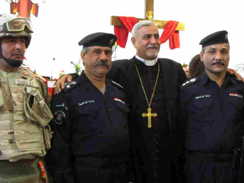 After delivering mass, Monsignor Pius Kasha poses with security officials who are guarding the Syriac Catholic church in the Mansour neighborhood in Baghdad.
