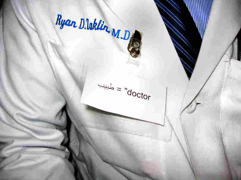Dr. Ryan Zaklin and other doctors at Spaulding Hospital are wearing name tags in English and Arabic to help their Libyan patients. There are also small sticky notes with English words written on them scattered throughout the hospital to help the patients learn terms for common objects.