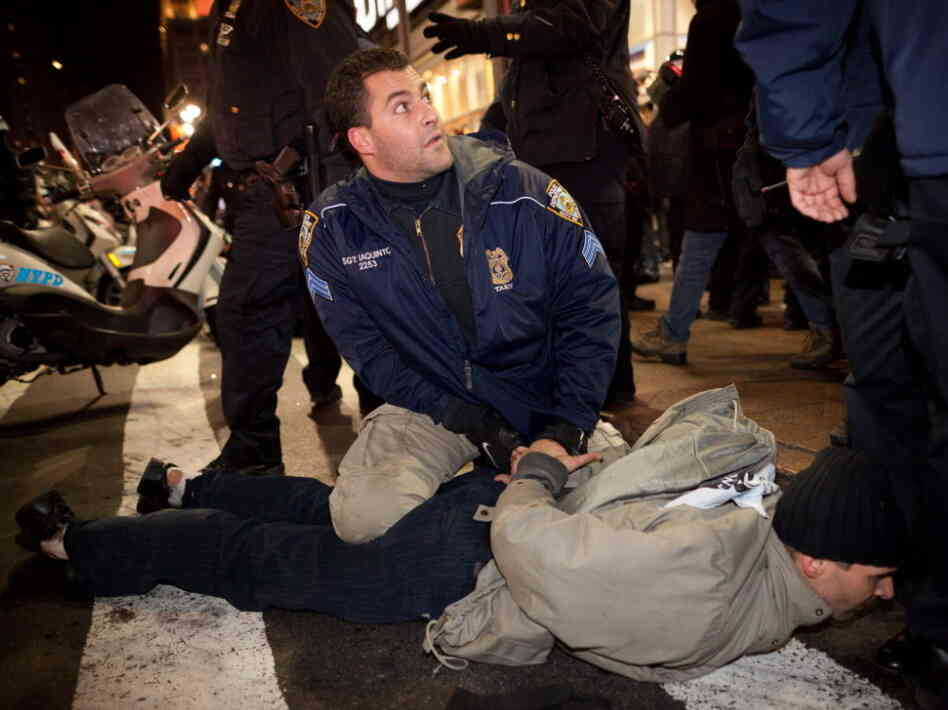 A police officer pins an Occupy Wall Street protester in New York City on Dec. 17. Police in different cities have found their own responses to the ongoing protests.