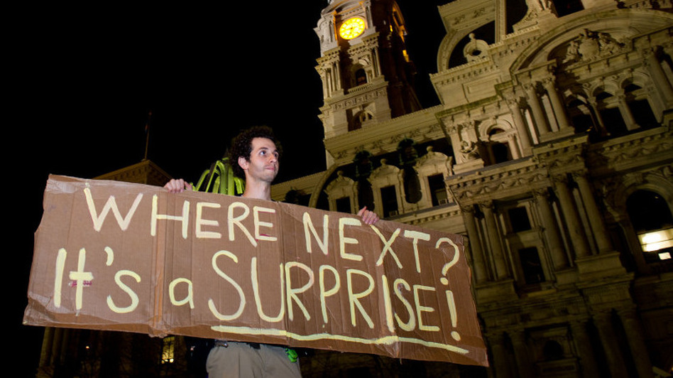 A protester holds a sign after a deadline to clear Occupy Philadelphia's Dilworth Plaza in late November. Occupy protesters across the country have found creative ways to continue their efforts after being evicted from public spaces.