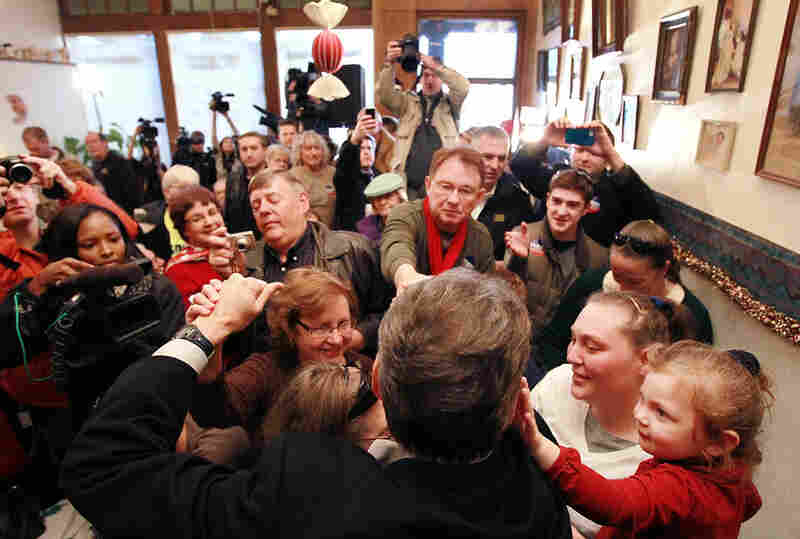 Republican Rick Perry (back to camera) greets supporters during a Dec. 27 campaign stop at the Main Street Cafe in Council Bluffs, Iowa.