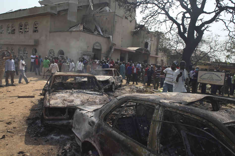 Onlookers gather around a destroyed car at a Catholic church bombed on Christmas Day. A violent Islamist group claimed responsibility for the deadly attack.