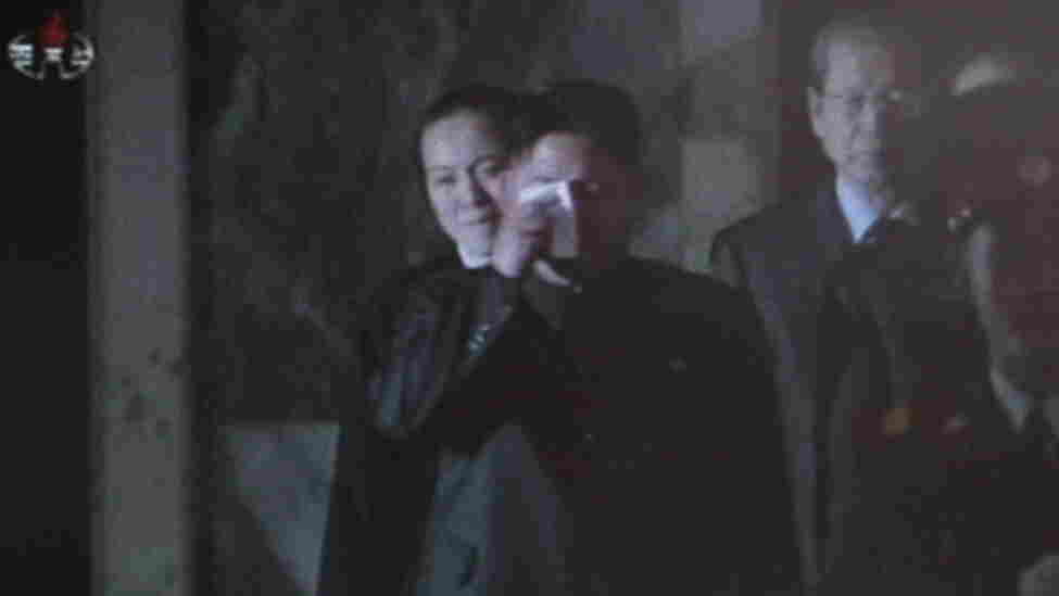 In this image made from North Korean television, Kim Jong Un, center, apparently cries as he pays respect to his father.