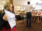 A young supporter backs former Massachusetts Gov. Mitt Romney as he speaks on Wednesday at Homer's Deli and Bakery in Clinton, Iowa.