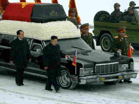 Kim Jong Un, center, walks with his hand on the limousine bearing his father Kim Jong Il's body earlier today in Pyongyang.
