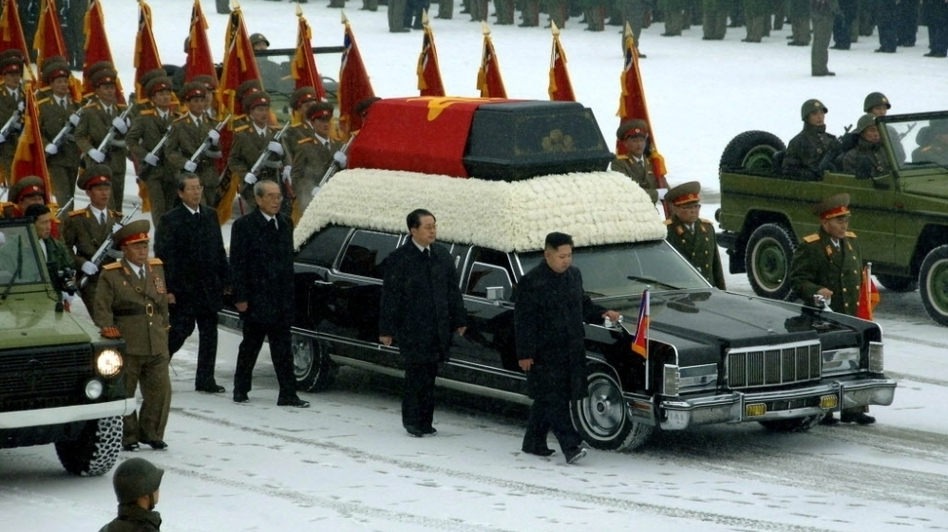 This photo provided by Korean Central News Agency (KCNA) shows Kim Jong Un, center, with his hand on the limousine bearing his father Kim Jong Il's body during the funeral procession in Pyongyang. (Korean Central News Agency)
