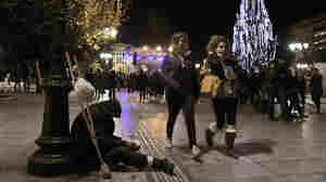 A homeless man begs for money during the launch of Christmas celebrations in Athens' central Syntagma Square, Dec. 9. Difficult economic times have meant subdued holiday activities — and even carolers, who traditionally receive money for their songs, are feeling the pinch.