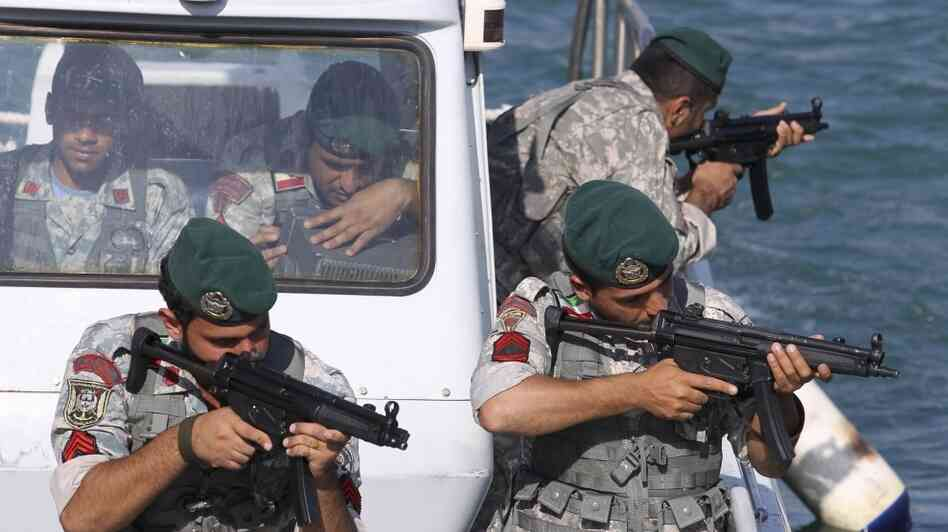 Members of the Iranian navy take positions during war-game exercises in the Sea of Oman on Wednesday. Iran's navy c