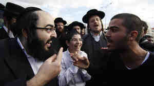 An ultra-Orthodox Jewish man (left) and a secular man argue during a protest against the strict religious codes favored by the ultra-Orthodox in the Israeli city of Beit Shemesh.