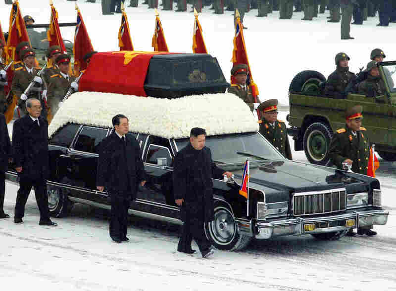 The heir apparent in North Korea, Kim Jong Un, in black at the front of the vehicle, walks besides the hearse carrying the body of his father and late leader Kim Jong Il at Kumsusan Memorial Palace.