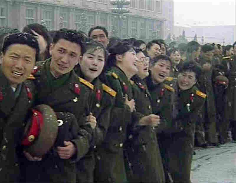 Military personnel react during Kim Jong Il's funeral procession in Pyongyang in this still image taken from video.