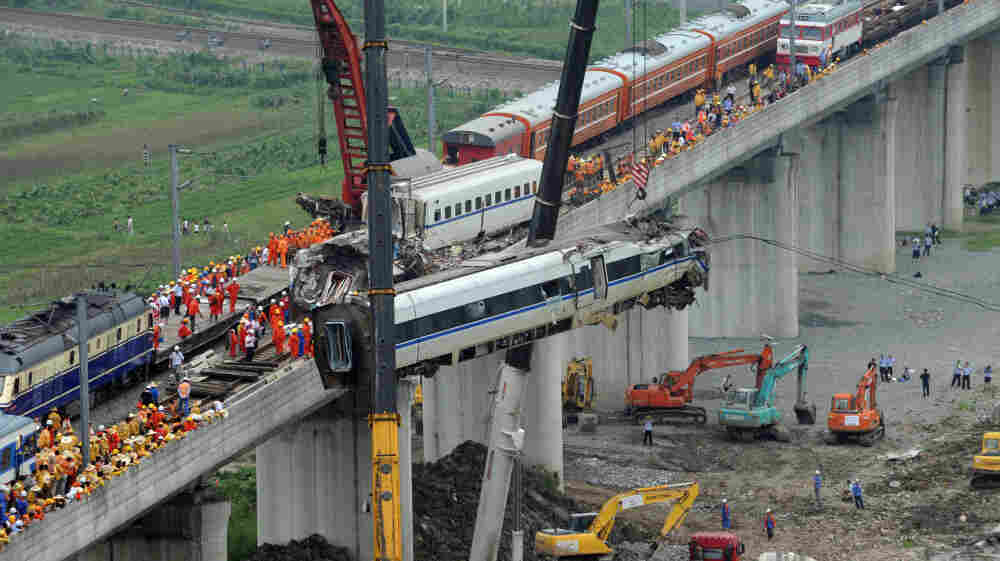 Workers clear mangled wreckage at the scene of a bullet train collision on July 24.