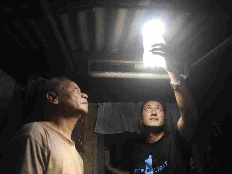 Illac Diaz inspects a solar light bulb with Siplicio Mondas, 73, in Manila. Diaz heads the nonprofit MyShelter Foundation, which is overseeing this solar lighting project.