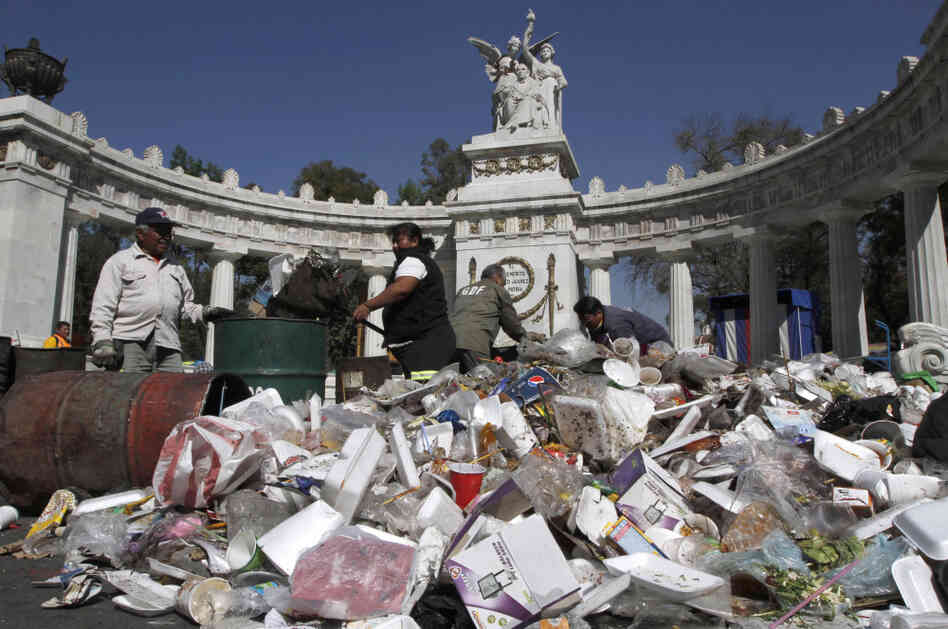 City workers remove piled up garbage that accumulated over the Christmas weekend in front of the Monument to Benito Juarez, one of Mexico's most important statesmen.